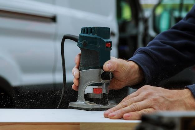 Lavoratori che usano il router elettrico per tagliare le strisce