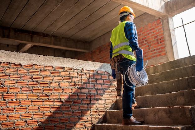 Lavoratori con dispositivi di protezione individuale supervisionare la costruzione della casa, il supervisore della costruzione, vedere il design degli interni, la costruzione di alloggi