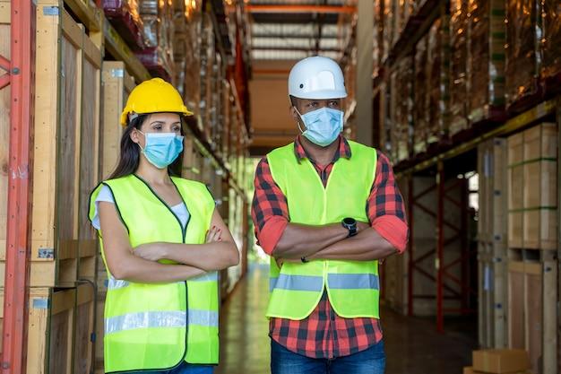 Lavoratori del magazzino che indossano maschera protettiva che lavora al magazzino, lavorano nella fabbrica di produzione industriale.