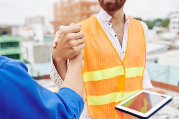 Lavoratori edili che agitano le mani