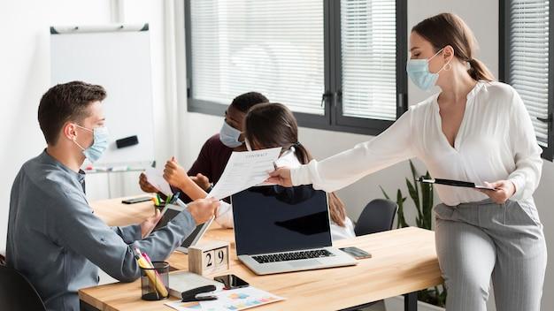 Lavoratori in ufficio durante la pandemia che indossano maschere mediche