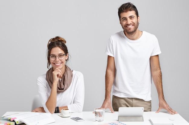 Lavoratori professionisti di sesso maschile e femminile in carica, lavorano al progetto di moderne tecnologie informatiche