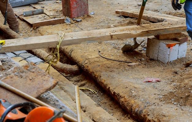 Lavoratori su una costruzione di strade, riparazione di vecchi tubi di sostituzione di installazione di conduttura di comunicazioni della città