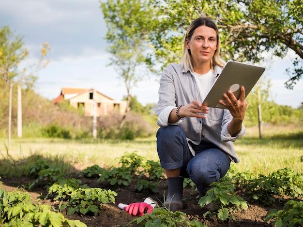 Lavoratrice agricola che controlla il suo giardino con una compressa