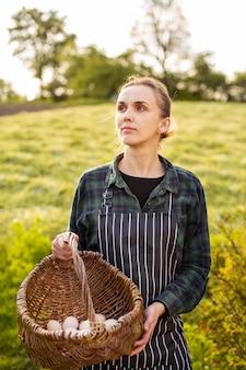 Lavoratrice agricola che raccoglie le uova