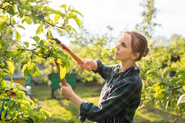 Lavoratrice agricola che rifila un albero
