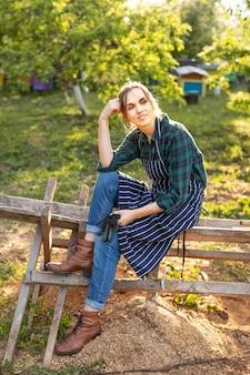 Lavoratrice agricola che si rilassa su un recinto
