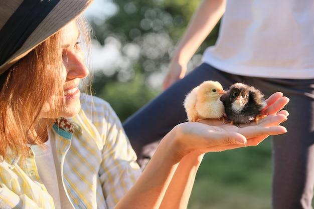 Lavoratrice agricola che tiene in mano due piccoli polli del neonato