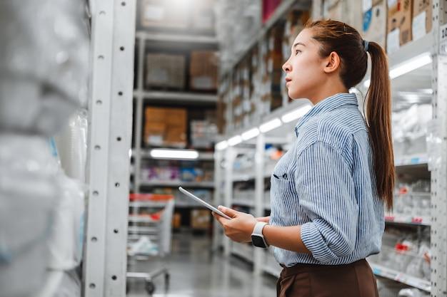 Lavoratrice asiatica che lavora con la compressa digitale che controlla le scatole