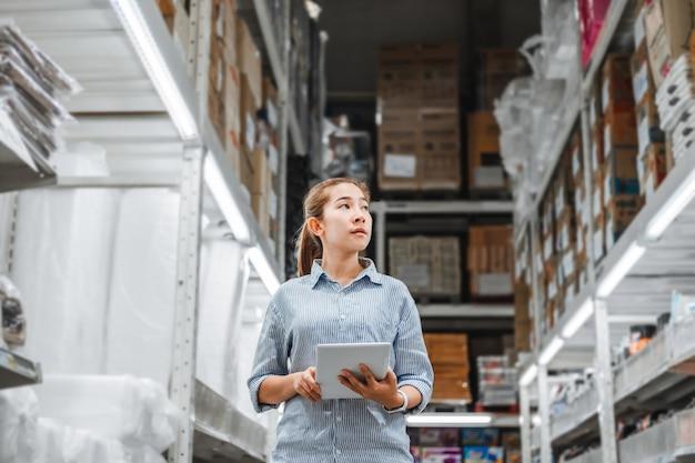 Lavoratrice asiatica che lavora con le caselle di controllo digitali della compressa