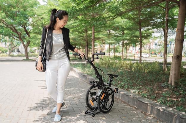 Lavoratrice asiatica che tiene la sua bici pieghevole