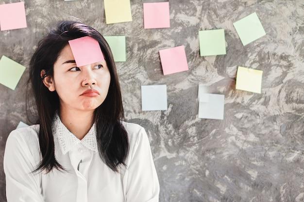 Lavoratrice asiatica non motivata con la nota appiccicosa