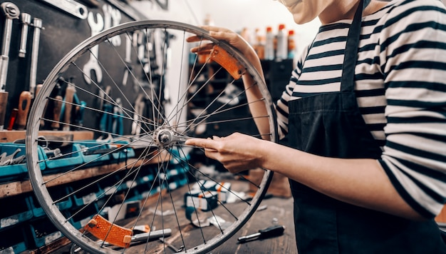 Lavoratrice caucasica sveglia che tiene e che ripara la ruota di bicicletta mentre stando nell'officina della bicicletta.