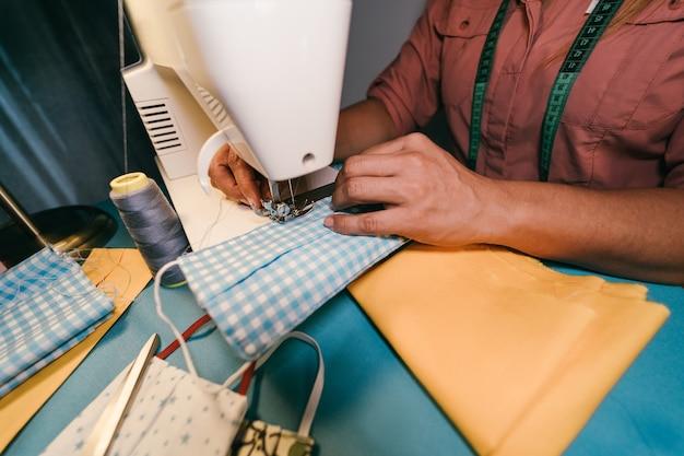 Lavoratrice che per mezzo della macchina per cucire mentre facendo le maschere mediche di modo del fronte