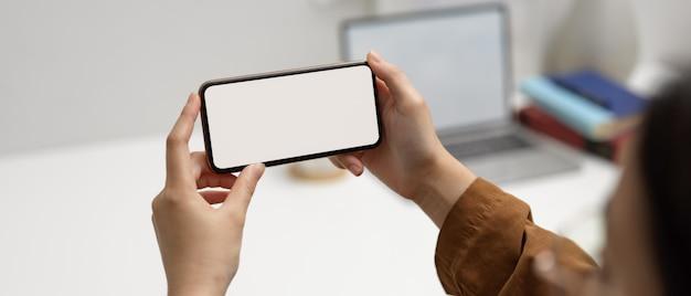 Lavoratrice che utilizza smartphone orizzontale del modello nella stanza dell'ufficio con il computer portatile e rifornimenti nel fondo vago