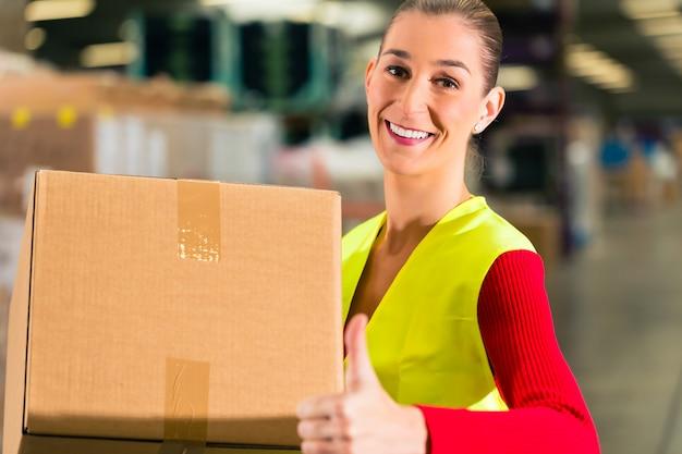 Lavoratrice con gilet protettivo detiene il pacchetto, in piedi presso il magazzino della società di spedizioni