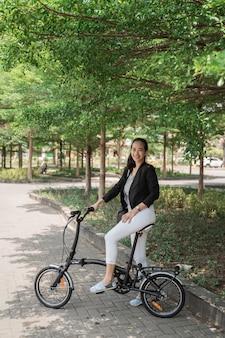 Lavoratrice pronta a guidare la sua bici pieghevole