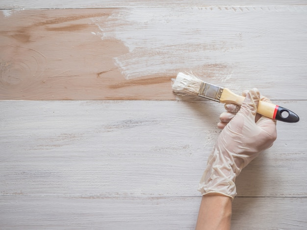 Lavori di riparazione su pittura. il pennello in mano dipinge il pavimento.