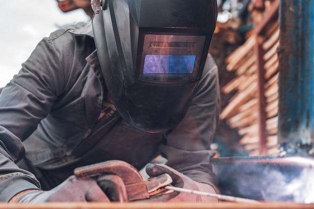 Lavori di saldatura, saldatura uomo in officina. carpenteria metallica e scintille. concetto di costruzione e industriale.