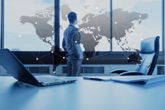 Lavori lo scrittorio dell'uomo d'affari con il computer portatile, concetto di affari di globalizzazione