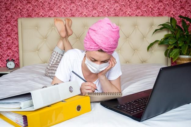 Lavoro a distanza dalla quarantena domestica. giovane ragazza caucasica sul letto in una maschera che fa i compiti. guarda il suo laptop e prende appunti su un quaderno.