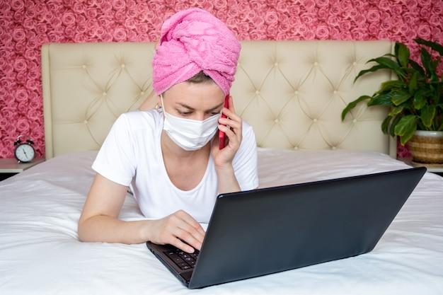 Lavoro a distanza dalla quarantena domestica. giovane ragazza caucasica sul letto in una maschera guarda il suo computer portatile e chiama il telefono per ordinare cibo.