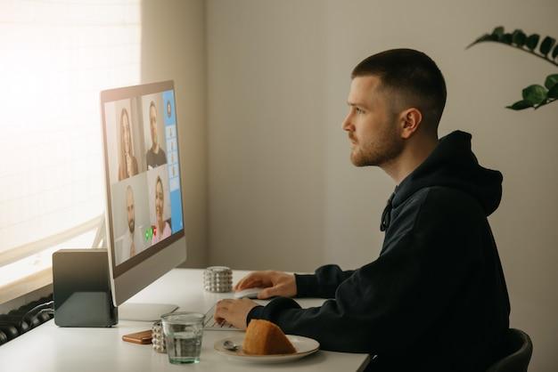 Lavoro a distanza. un uomo durante una videochiamata con i suoi colleghi sul computer desktop. un collega che lavora intensamente da casa per un briefing online.