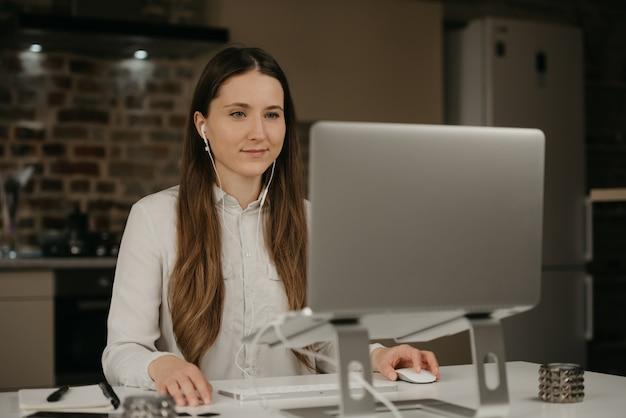 Lavoro a distanza. una donna caucasica con le cuffie che lavora in remoto sul suo computer portatile. una donna d'affari in una camicia bianca fare affari nel suo posto di lavoro a casa.