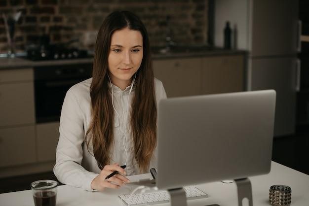 Lavoro a distanza. una donna caucasica del brunette con le cuffie che lavora a distanza sul suo computer portatile. una signora in una camicia bianca che fa affari nel suo posto di lavoro a casa.
