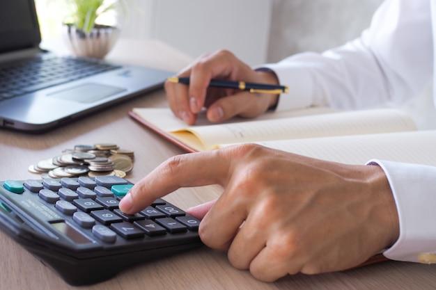 Lavoro asiatico dell'uomo d'affari con i calcolatori per calcolare le informazioni di conto