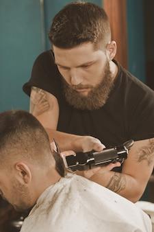 Lavoro attento. ritratto verticale di un barbiere che lavora al taglio di capelli con un rifinitore