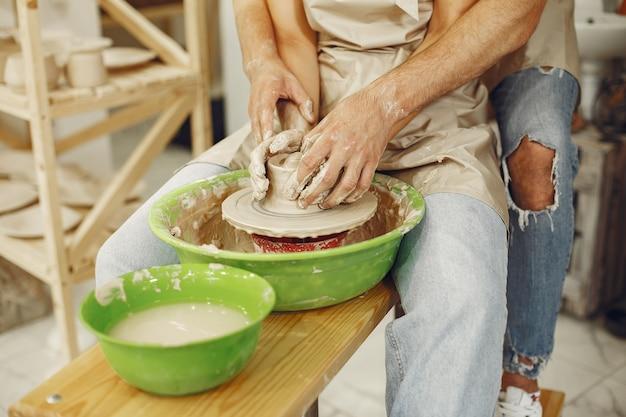 Lavoro creativo reciproco. giovane bella coppia in abiti casual e grembiuli. persone che creano una ciotola su un tornio in uno studio di argilla.
