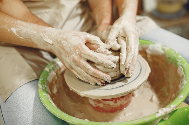 Lavoro creativo reciproco. mani che creano una ciotola su un tornio in uno studio di argilla.