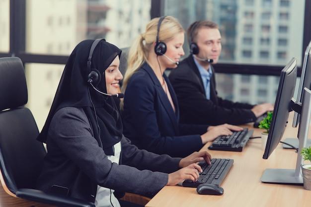 Lavoro del gruppo di affari corporativi consulente dello scrittorio di servizio personale di servizio di assistenza al cliente che parla sull'auricolare nel call center