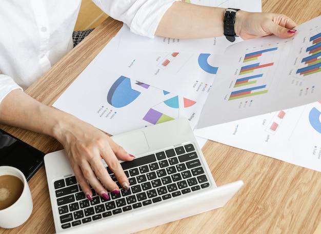 Lavoro di gruppo di affari che analizza il computer portatile moderno di strategia dei grafici e dei grafici