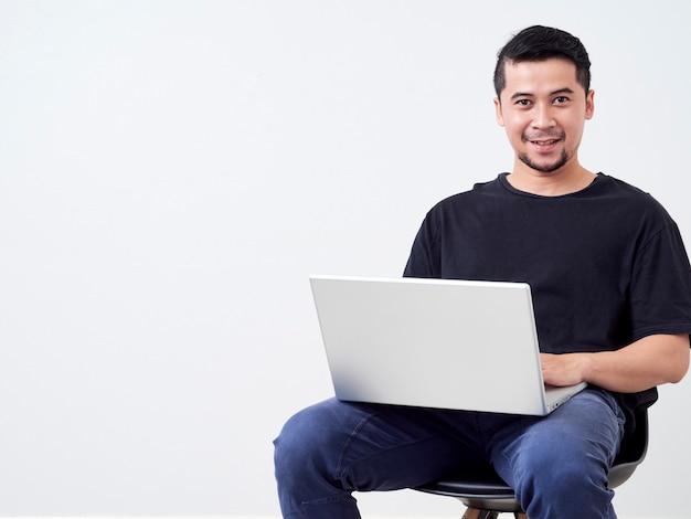 Lavoro di seduta del giovane con il computer portatile