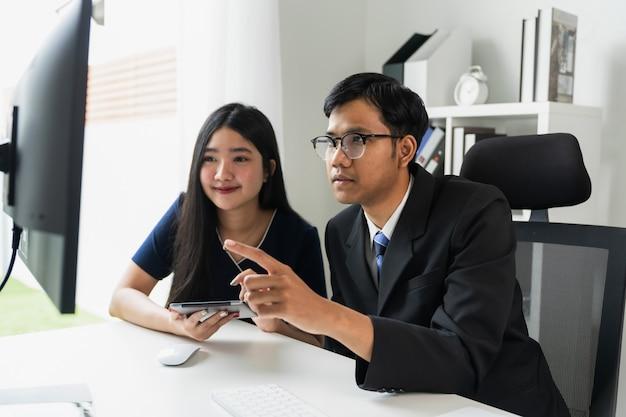 Lavoro di squadra asiatico di affari facendo uso del computer con la compressa e riporta i grafici.