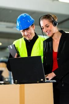 Lavoro di squadra, autista di magazzinieri o carrelli elevatori e supervisore femminile con laptop, cuffie e telefono cellulare, presso il magazzino della società di spedizioni un carrello elevatore