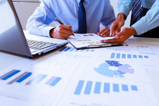 Lavoro di squadra di affari che discute le idee e che progettano sulla sintesi dei profitti nella sala riunioni.