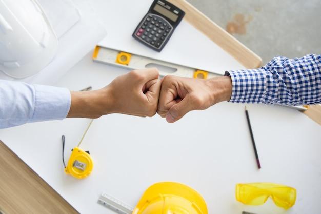 Lavoro di squadra di successo con l'appaltatore. i soci dell'ingegnere e dell'architetto danno il pugno dopo l'accordo completo.