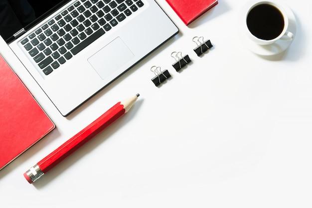 Lavoro di ufficio con laptop, tazza di caffè, accessori rossi