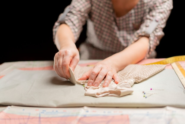 Lavoro femminile del sarto nell'officina sulla tavola scura