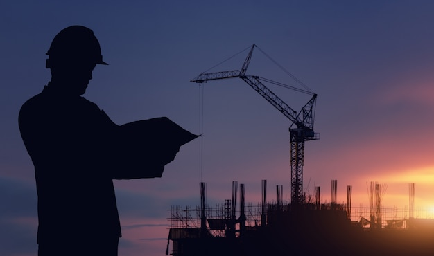 Lavoro in piedi dell'ingegnere della siluetta su costruzione.