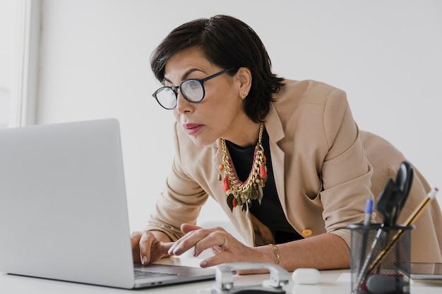 Lavoro senior sul colpo medio del computer portatile