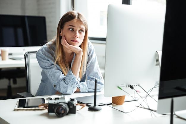 Lavoro serio della giovane donna in ufficio facendo uso del computer