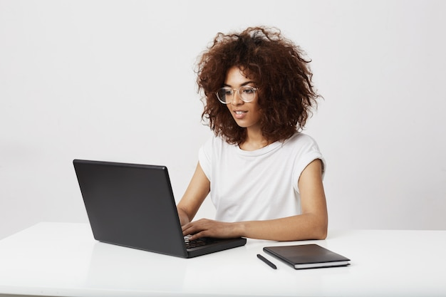 Lavoro sorridente di signora africana di affari al computer portatile sopra la parete bianca.