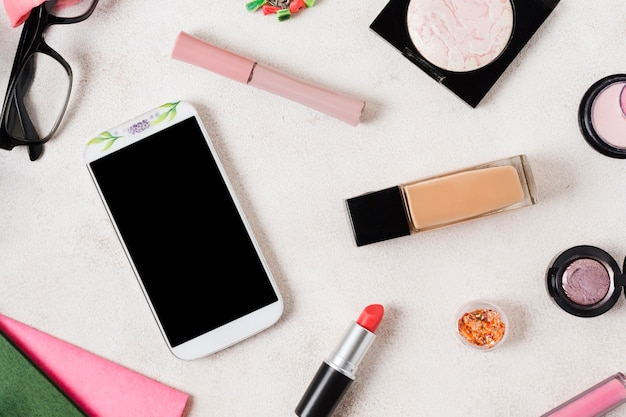 Lay out di prodotti per il trucco e smartphone