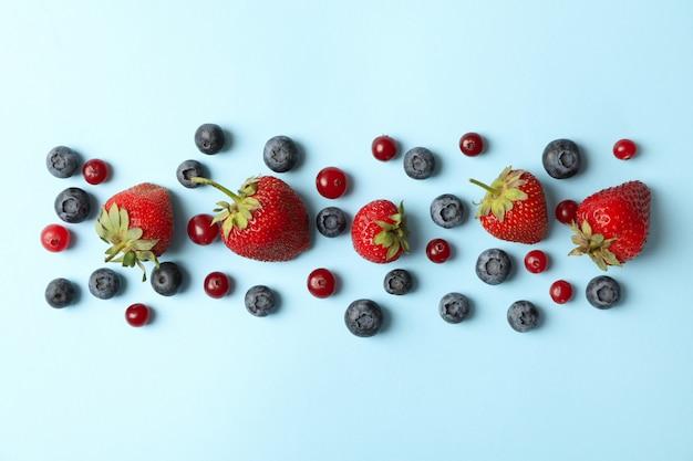 Lay piatto con frutti di bosco freschi su sfondo blu, vista dall'alto