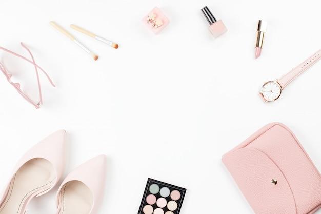Lay piatto con pompe rosa pastello, cosmetici, borsa su bianco, copia dello spazio