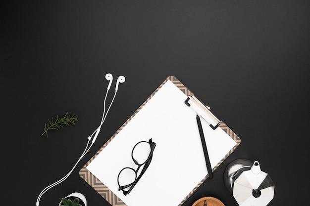 Lay piatto del desktop con blocco note e occhiali